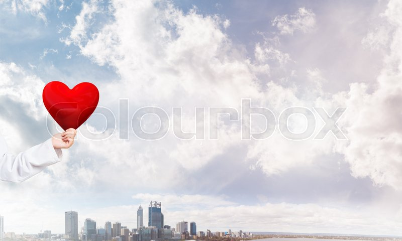Stock image of 'Close view of woman doctor against city background holding red heart'