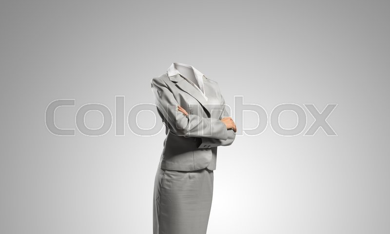 Stock image of 'Headless businesswoman with arms crossed on chest on gray background'