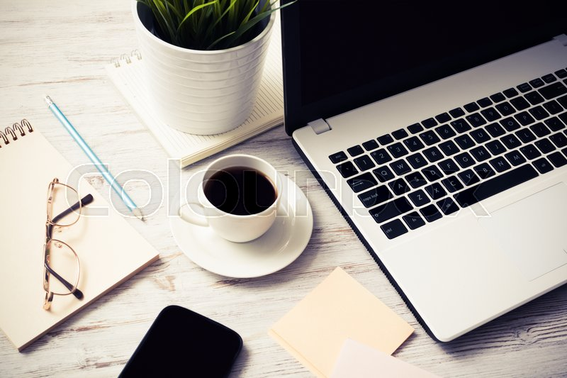 Stock image of 'Still life photo of laptop notepad coffee glasses and other stuff on wooden table'