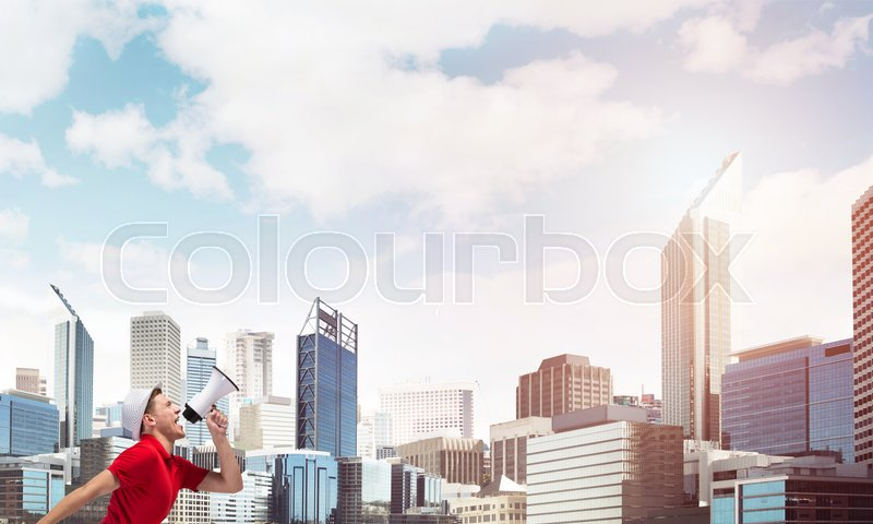 Stock image of 'Young man against city background screaming emotional in megaphone'