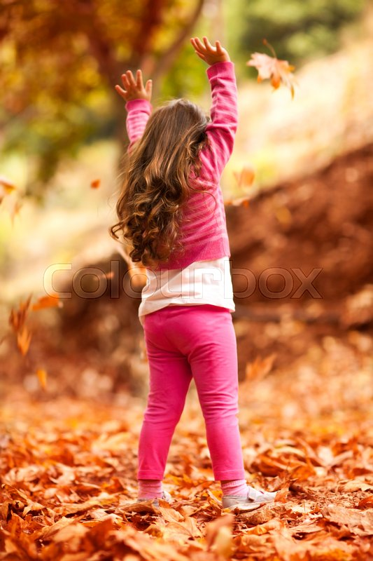Stock image of 'Happy little girl in autumn park, rear view of a nice child throwing up dry tree leaves, playing outdoors in a warm fall day, happy carefree childhood'