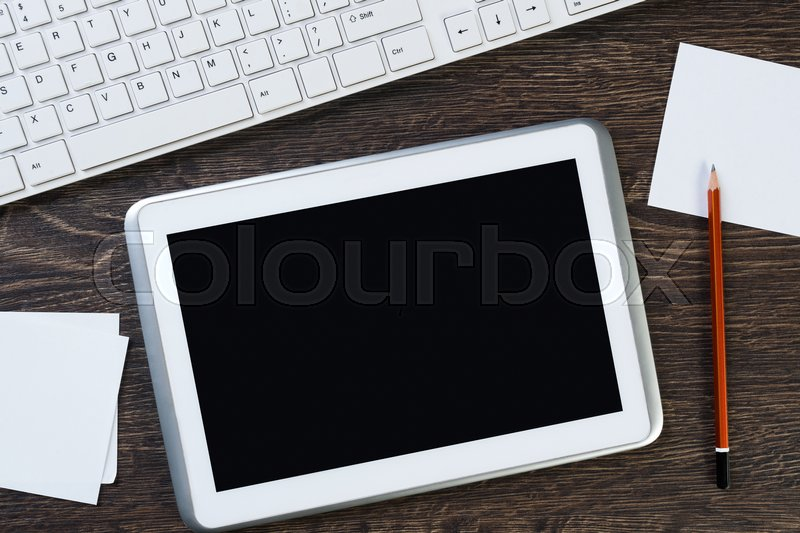 Stock image of 'White tablet pc and stationary on wooden table'