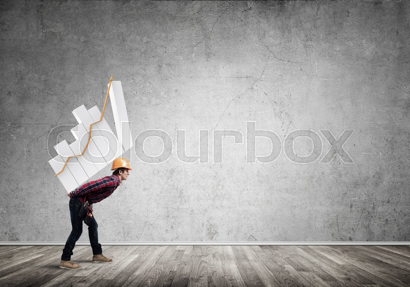 Stock image of 'Young man builder carrying growing graph on his back'