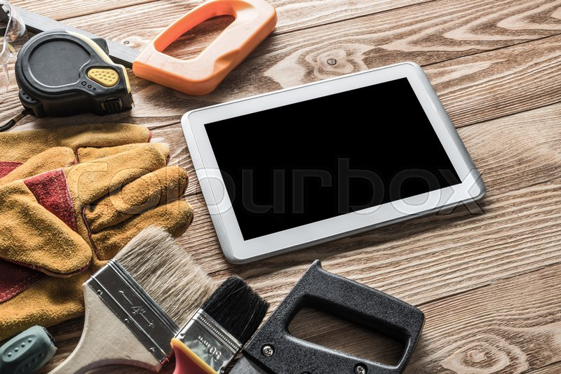 Stock image of 'Variety of tools of builder and tablet pc on wooden texture table'