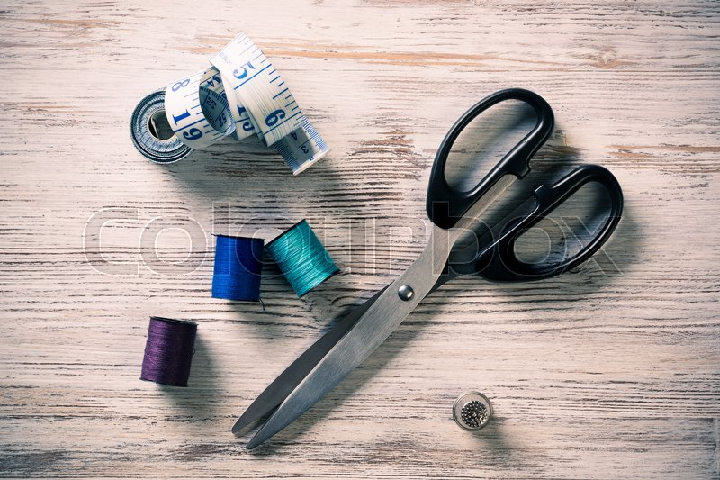 Stock image of 'Old scissors bobbins threads and tape on wooden table'