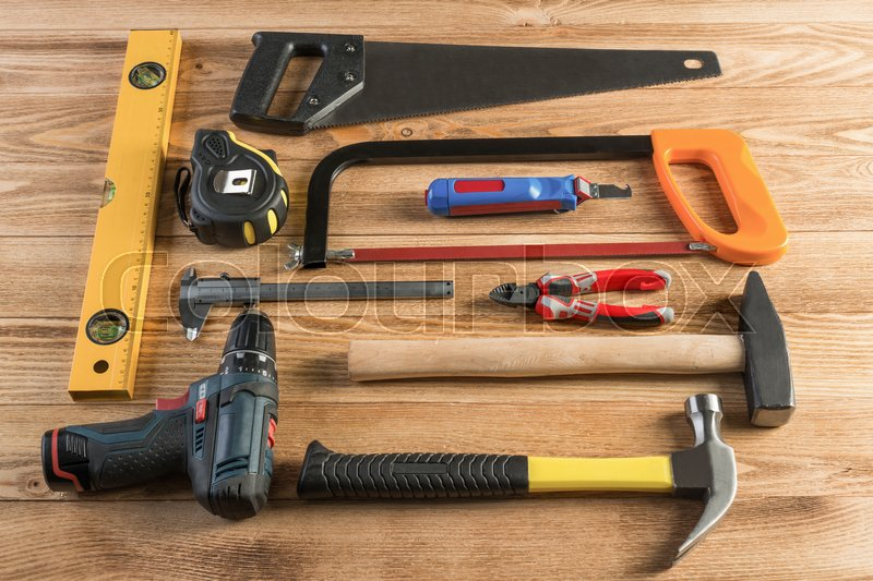 Stock image of 'Variety of repair tools on wooden surface'