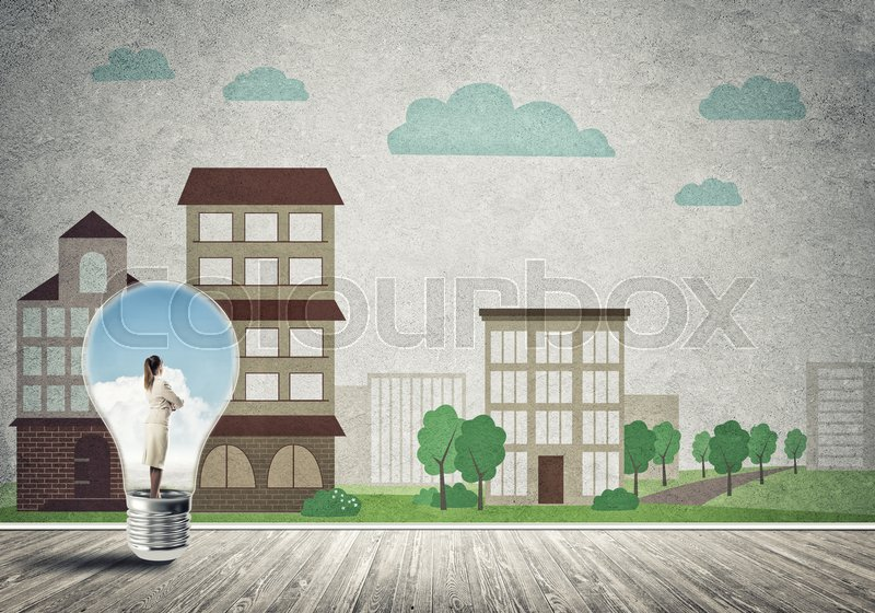 Stock image of 'Businesswoman inside light bulb against city drawn concept'