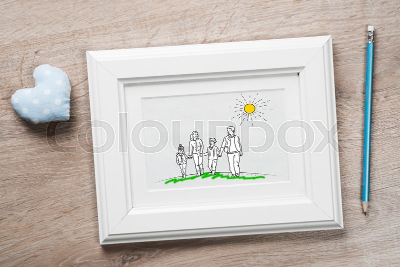 Stock image of 'Photo frame with happy family drawing on wooden table'
