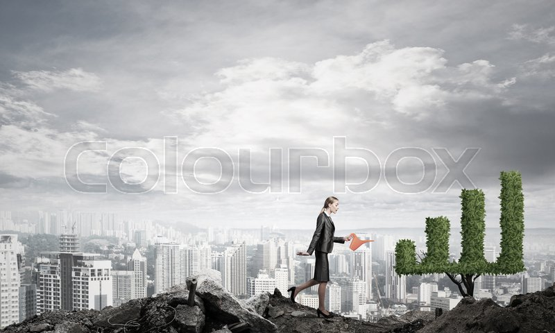Stock image of 'Young attractive businesswoman watering symbol chart plant in ground with can against the backdrop of the city'