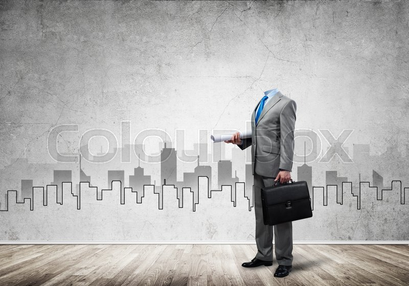 Stock image of 'Headless engineer man with papers and case in hand against construction background'