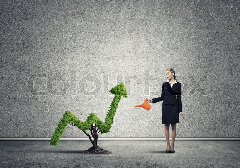 Stock image of 'Young attractive businesswoman watering plant in ground with can'