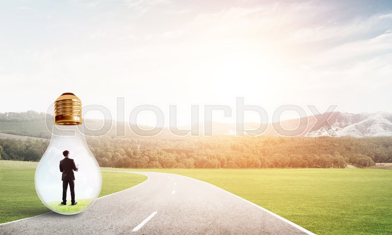 Stock image of 'Young businessman trapped inside of light bulb on asphalt road'