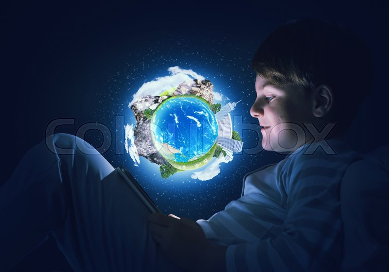 Stock image of 'Teenage boy in pajamas lying in bed using tablet pc. Elements of this image are furnished by NASA'