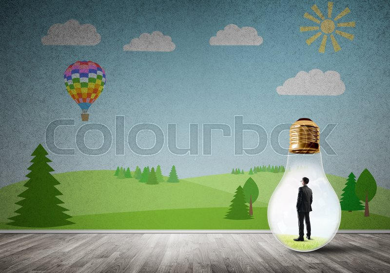 Stock image of 'Businessman inside light bulb in room against nature drawn concept'