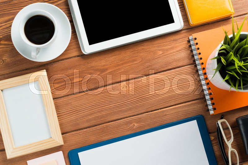 Stock image of 'Still life photo of tablet notepad coffee glasses and other stuff on wooden table'
