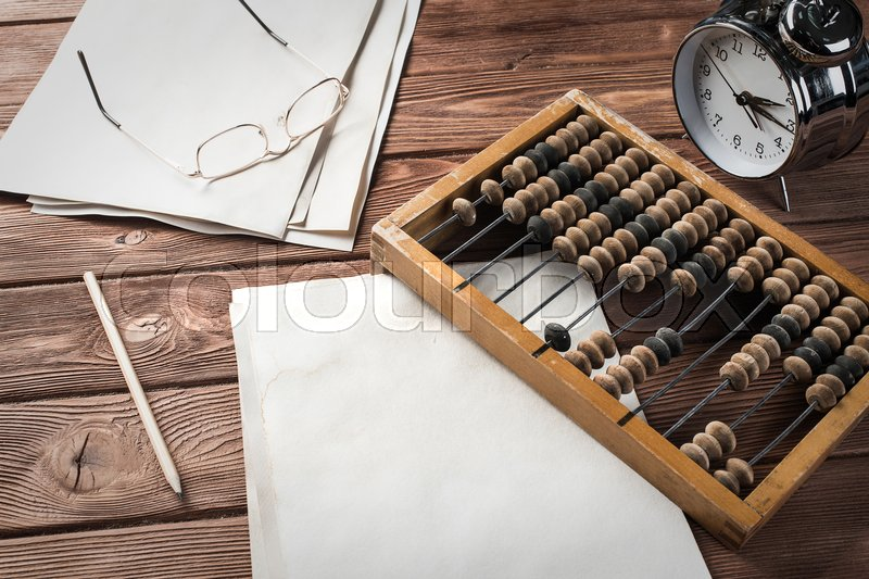 Stock image of 'Vintage abacus envelopes and alarm clock on wooden table'