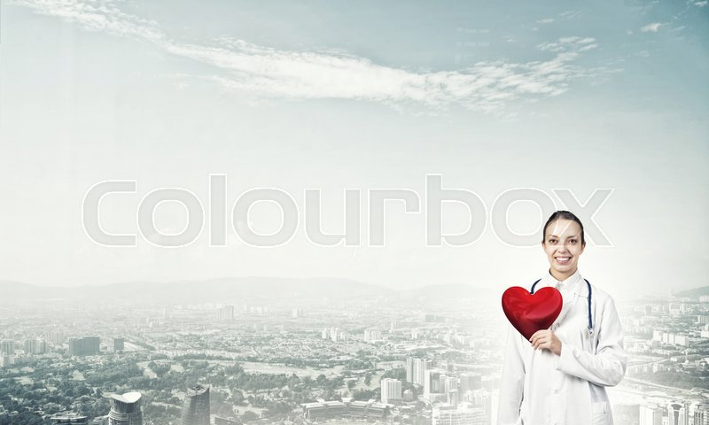 Stock image of 'Young woman doctor against city background holding red heart'