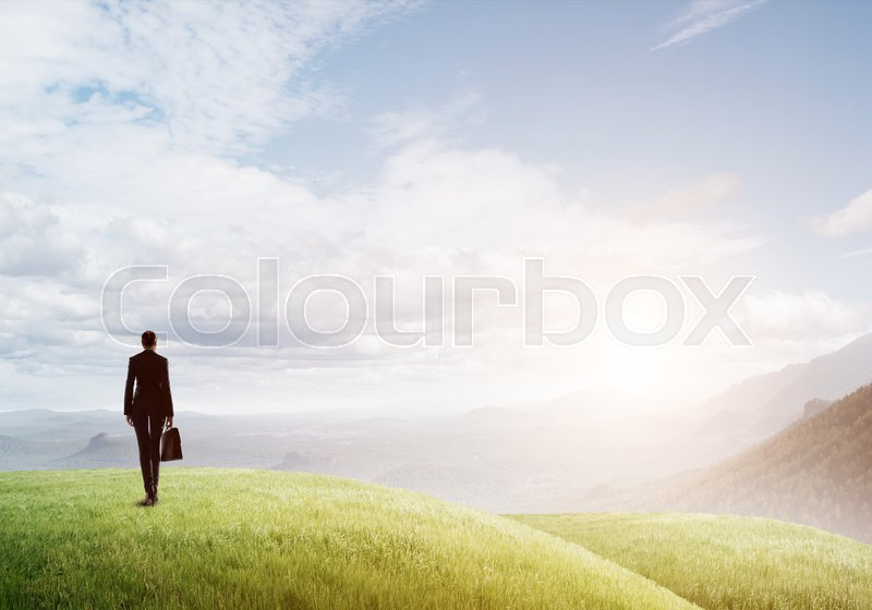 Stock image of 'Elegant businesswoman standing on green hill and looking ahead'