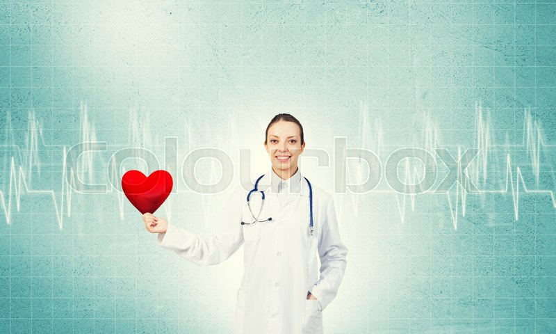 Stock image of 'Young woman doctor against blue background holding red heart'