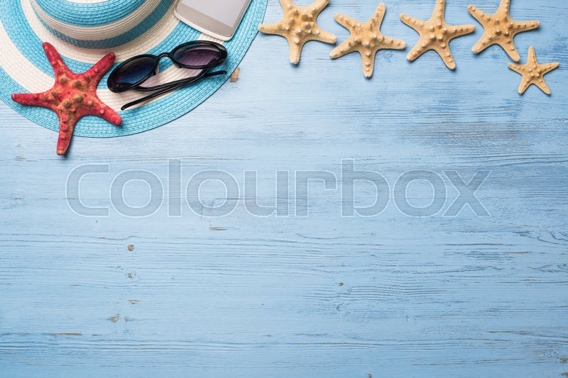 Stock image of 'Straw hat sunglasses smartphone and photocamera among sea shells and stones on wooden surface'