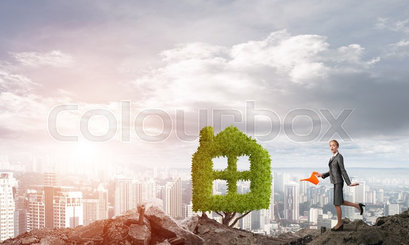 Stock image of 'Young attractive businesswoman watering plant in ground with can against the backdrop of the city'