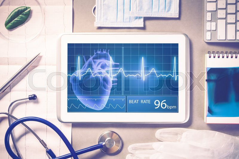 Stock image of 'White tablet pc and doctor tools on gray surface'