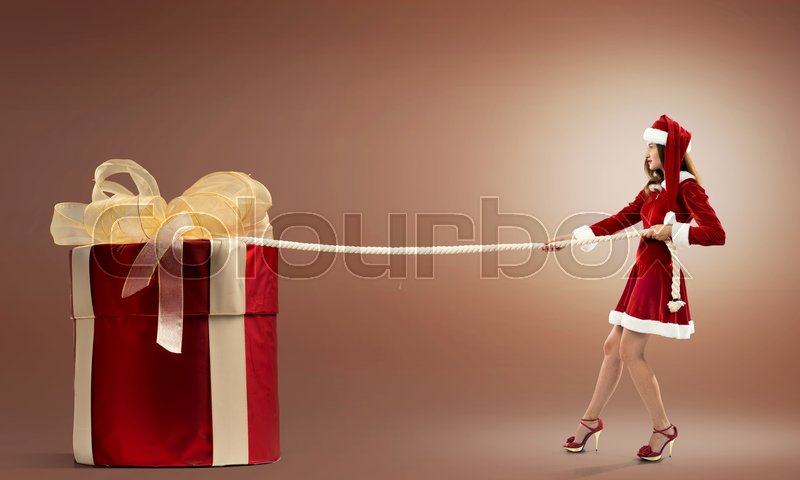 Stock image of 'Santa woman pulling huge red gift box'