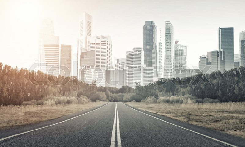 Stock image of 'Natural landscape with asphalt road and modern city'