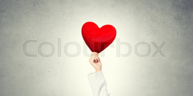 Stock image of 'Hand of woman doctor against gray background holding red heart'
