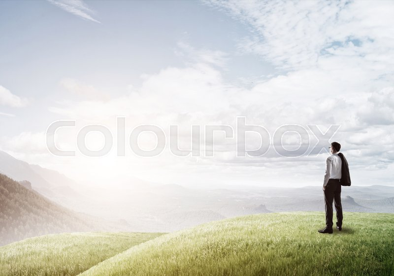 Stock image of 'Elegant businessman standing on green hill and looking ahead'