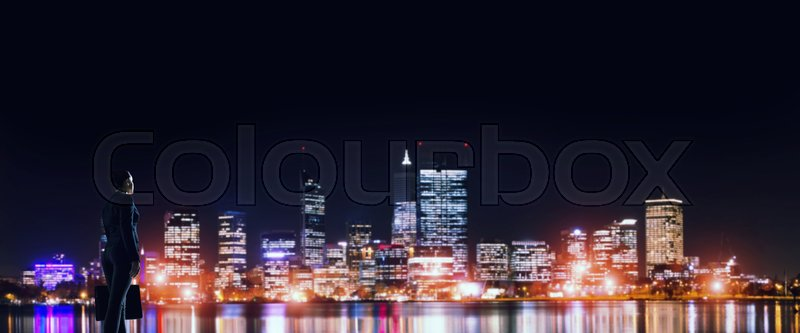 Stock image of 'Businesswoman standing with back against night city panoramic view'