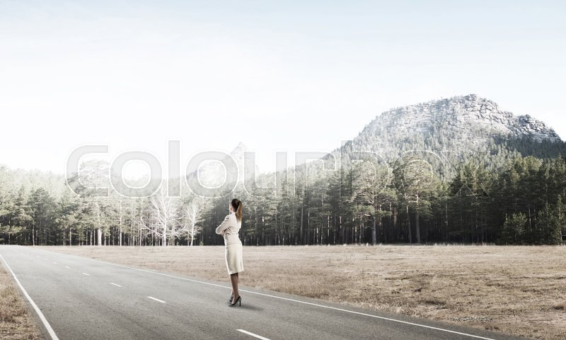 Stock image of 'Elegant businesswoman on road standing with back and looking ahead'