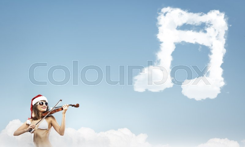 Stock image of 'Young woman in swimming suit and santa hat playing violin'