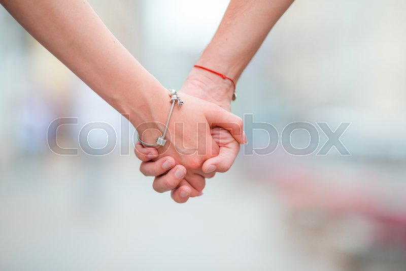 Stock image of 'Close up of girl and boy holding each other hands in city outdoor'