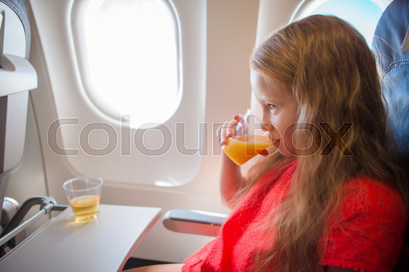 Stock image of 'Adorable little girl traveling by an airplane. Kid drinking orange juice sitting near aircraft window'