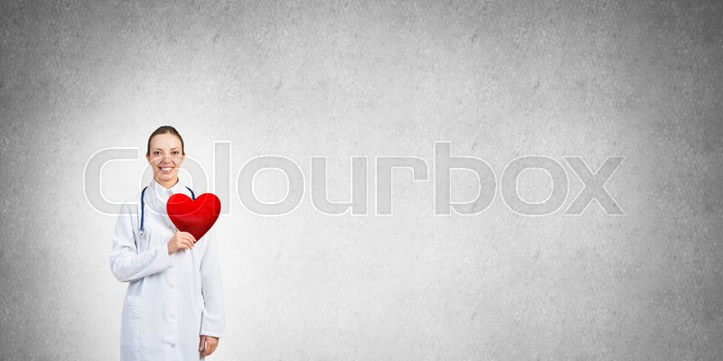 Stock image of 'Young woman doctor against gray background holding red heart'