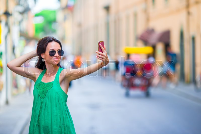 Stock image of 'Woman take selfie by her smartphone in city. Young attractive tourist taking self photo outdoors in italian city'
