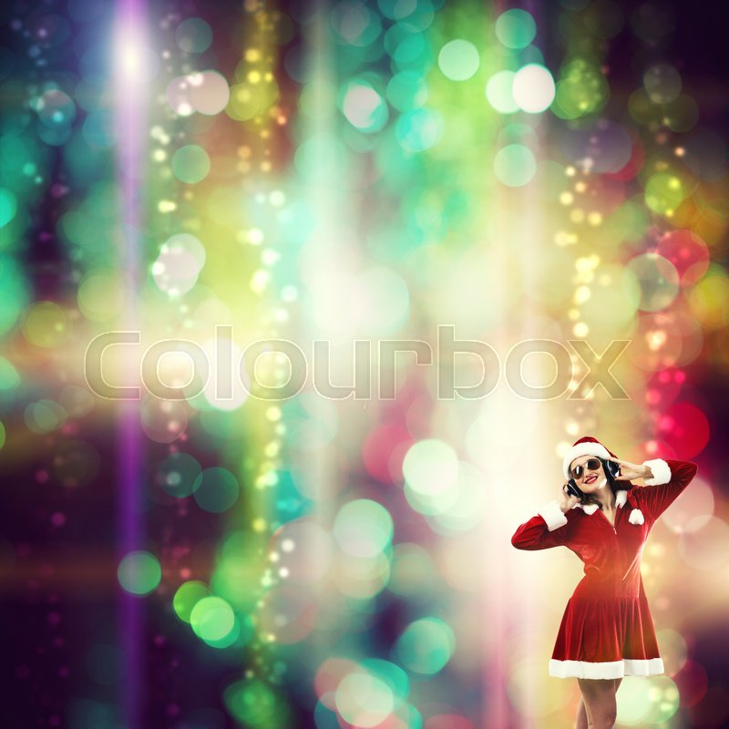 Stock image of 'Beautiful young woman in Santa Claus clothes and headphones over bokeh background'