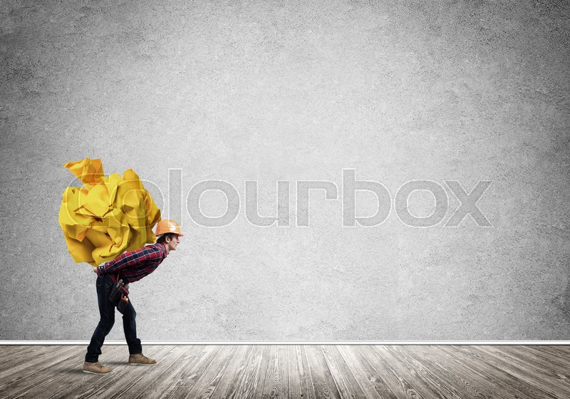 Stock image of 'Builder man carrying paper ball on his back'