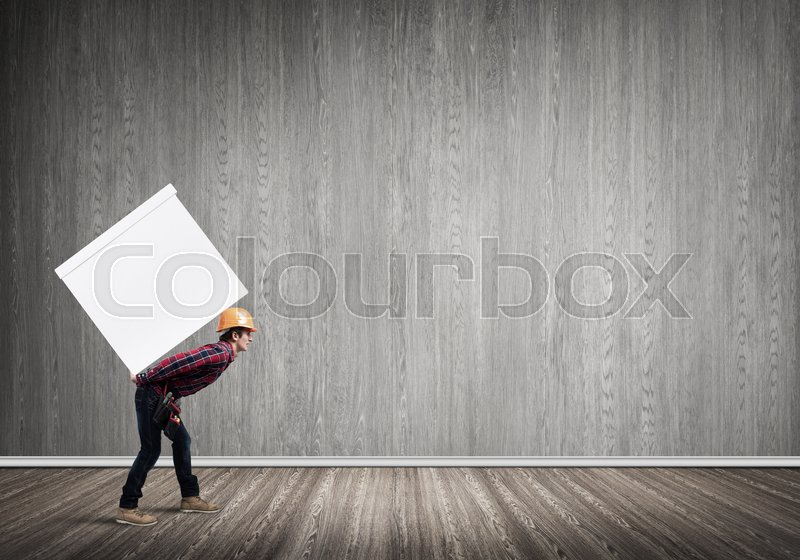 Stock image of 'Man carrying on his back large box'