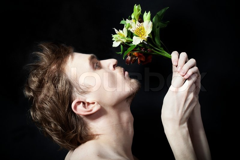 Face of the young men sniffing bouquet of flowers on a black ...