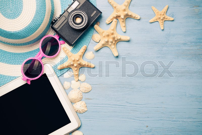 Stock image of 'Straw hat sunglasses and photocamera among sea shells and stones on wooden surface'
