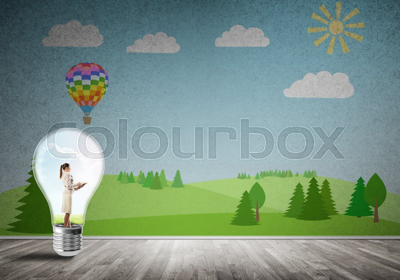 Stock image of 'Businesswoman inside light bulb in room against nature drawn concept'