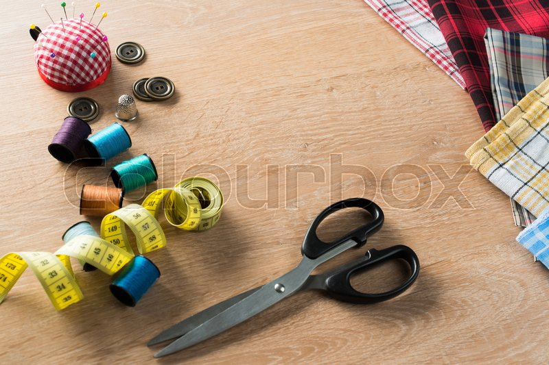 Stock image of 'Old scissors bobbins threads material on wooden table'