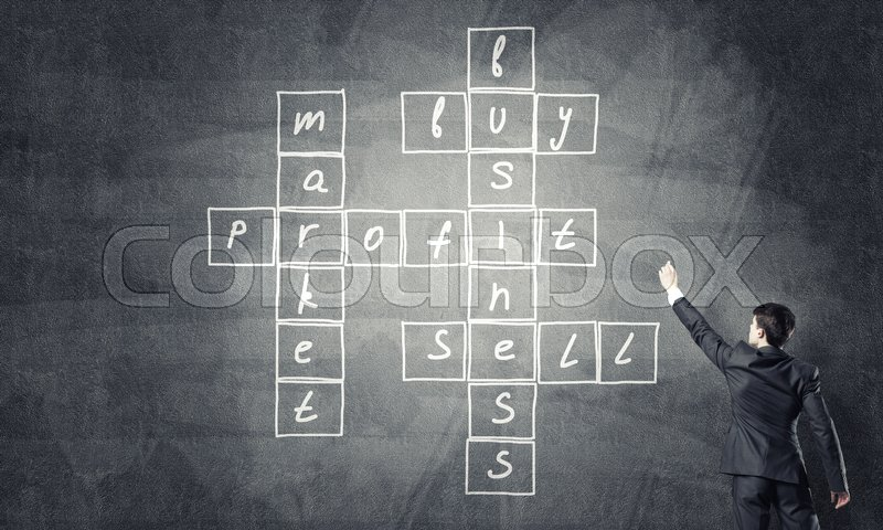 Stock image of 'Businessman standing with back and drawing crossword on blackboard'