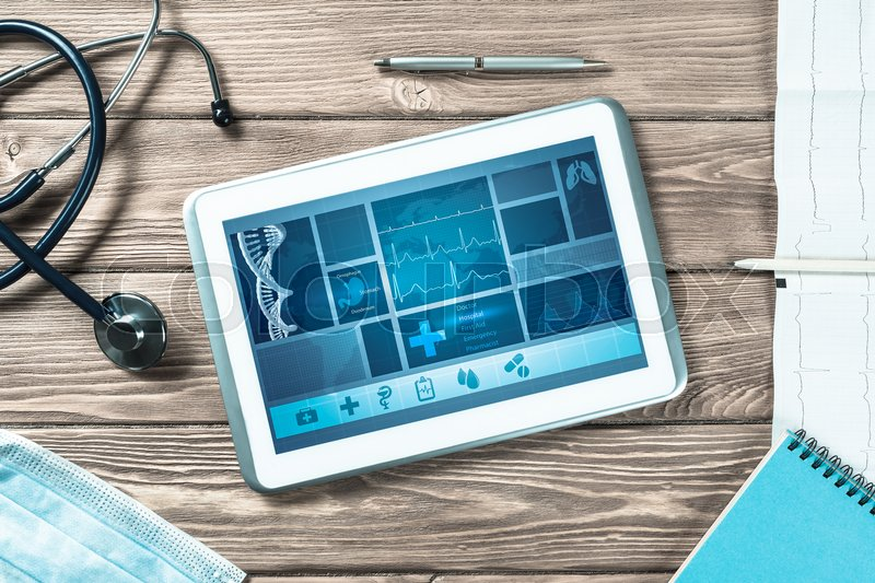 Stock image of 'White tablet pc and doctor tools on wooden table'