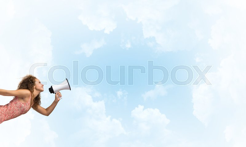 Stock image of 'Young woman shouting in megaphone with blue sky background'