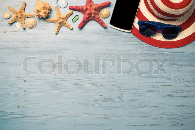 Stock image of 'Straw hat sunglasses smartphone among sea shells and stones on wooden surface'