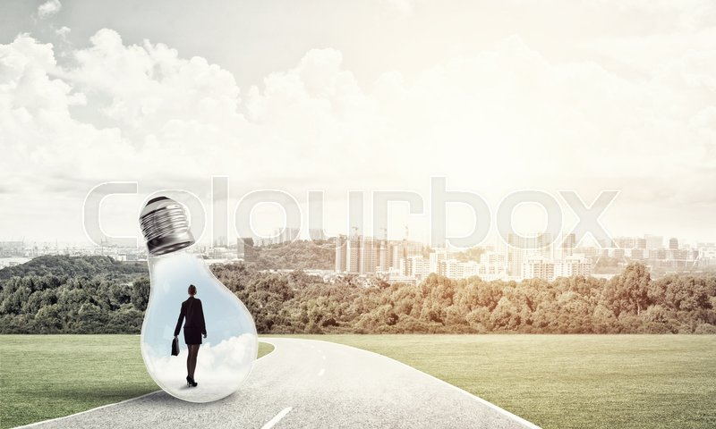 Stock image of 'Young businesswoman trapped inside of light bulb on countryside road'