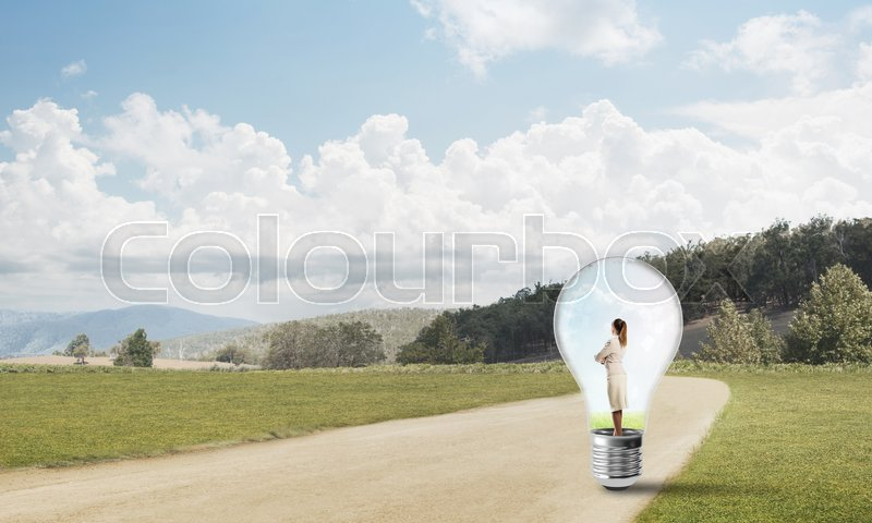 Stock image of 'Young businesswoman trapped inside of light bulb on road'